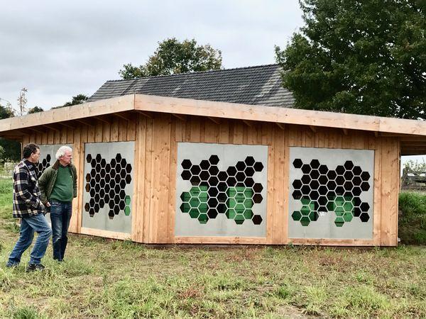 Design bijenstal: door de honingraatgaten in metaal, vliegen de bijen naar de kasten.